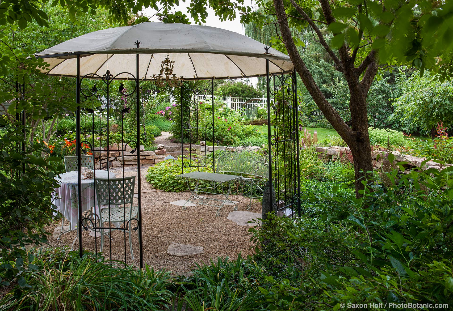 Free standing pergola over gravel patio with intimate dining area in Minnesota summer garden
