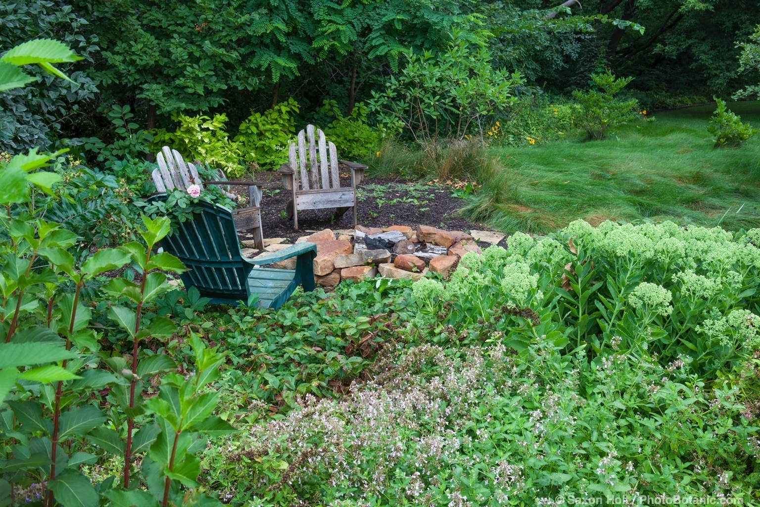Chairs around outdoor fireplace at edge of Minnesota garden