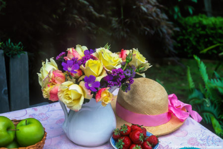 Rose 'Summer Fashion' in rose bouquet on table in country garden with straw hat
