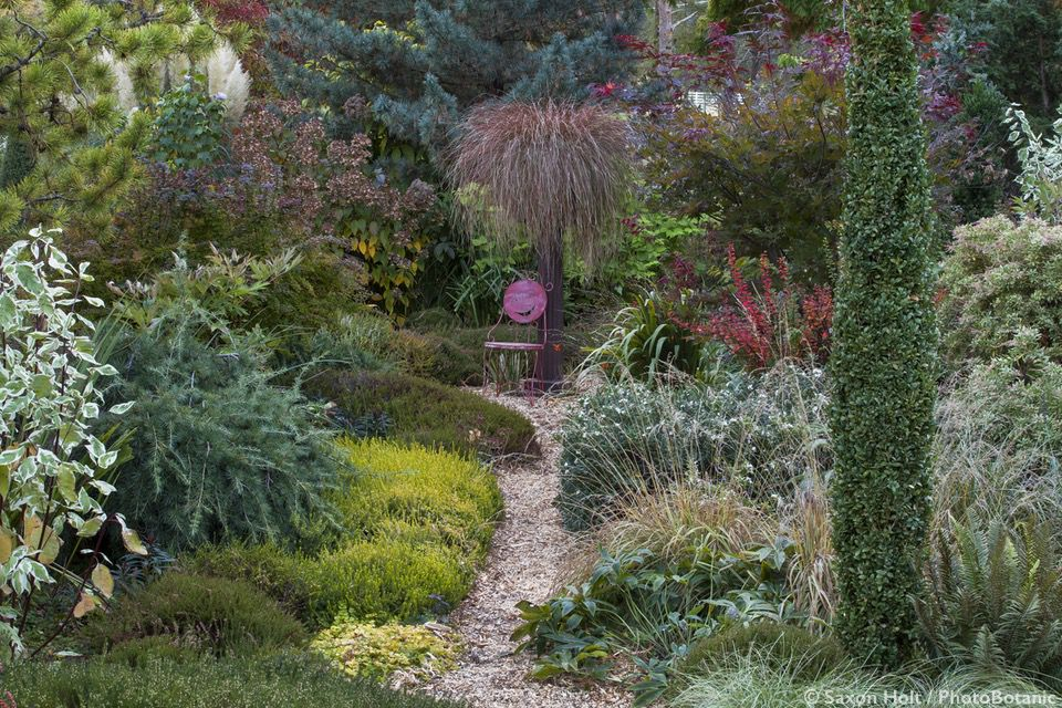 Path through mixed borders toward whimsical chair focal point in O'Byrne Oregon garden